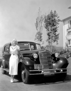 1930: American film actress Jean Harlow (1911 - 1937) poses with her new Cadillac V-12 motor car. (Photo by Margaret Chute)