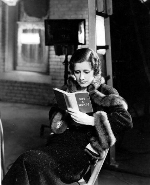 Irene Dunne reading on set