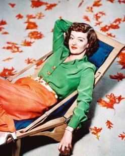 American actress Bette Davis (1908 - 1989), relaxing in a deckchair surrounded by autumn leaves, circa 1940.